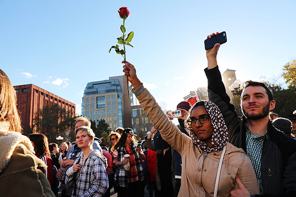 Person holding a rose among other protestors
