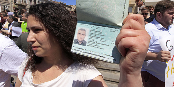 A woman holding up a passport.