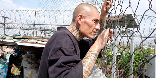 A man with tattoos looks through a chain-link fence