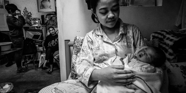 A woman holding a newborn baby