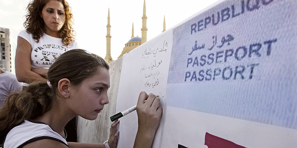 A young woman writing on a large sign