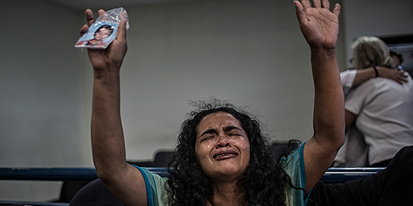 A woman crying and holding a photo above her head