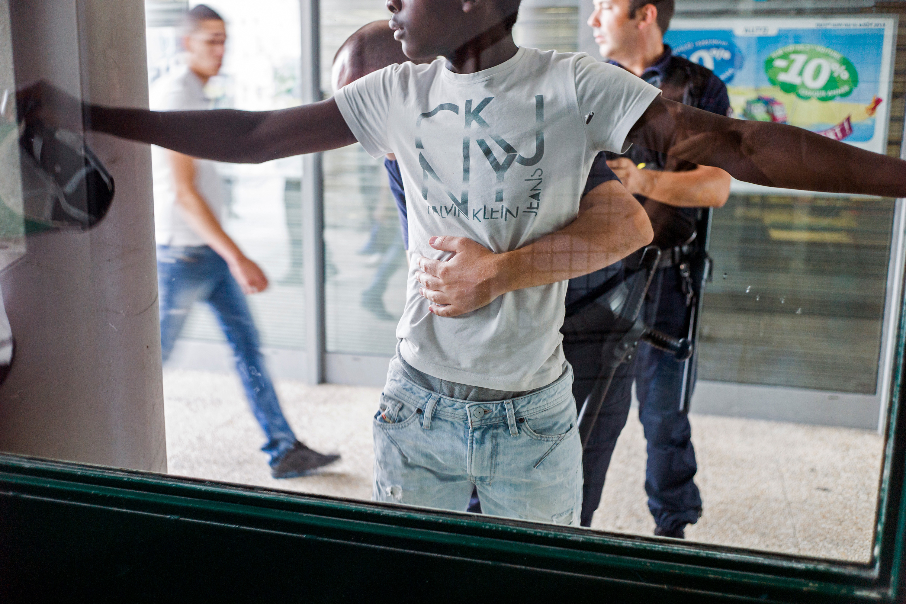 A man pressed up against a window with arms spread.