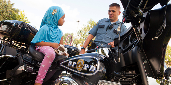 A police officer stands by young girl sitting on a police motorcycle