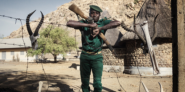 A guard holding a rifle and leaning on a barbed wire fence