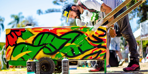 A man spray-painting a pushcart