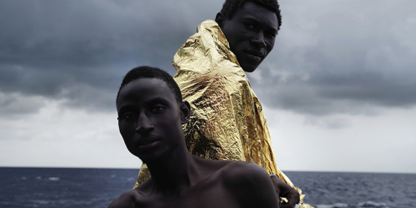 Two men on a boat, one wearing a gold-colored blanket