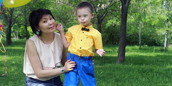 Aigul Shakibayeva kneeling next to her son