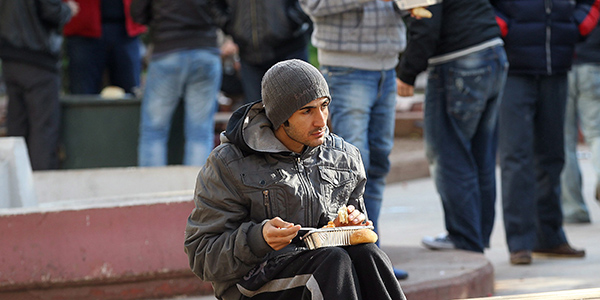 A man sitting on a bench eating