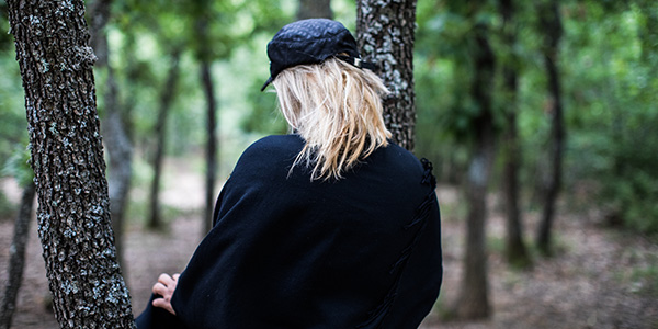 The back of a woman wearing a hat in a forest