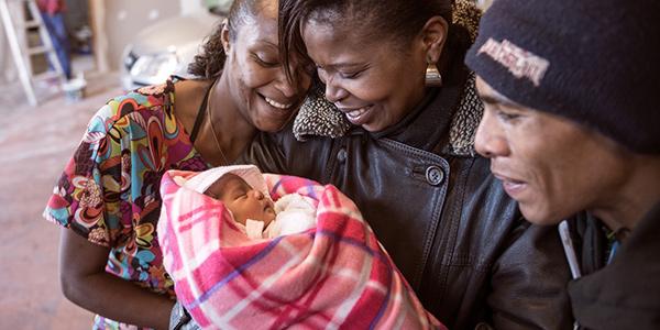 People looking at a sleeping newborn baby