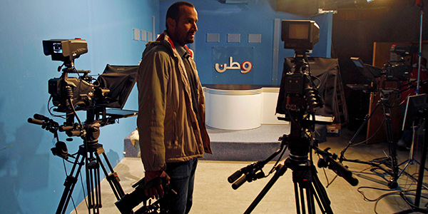 A man holding a camera in a television studio