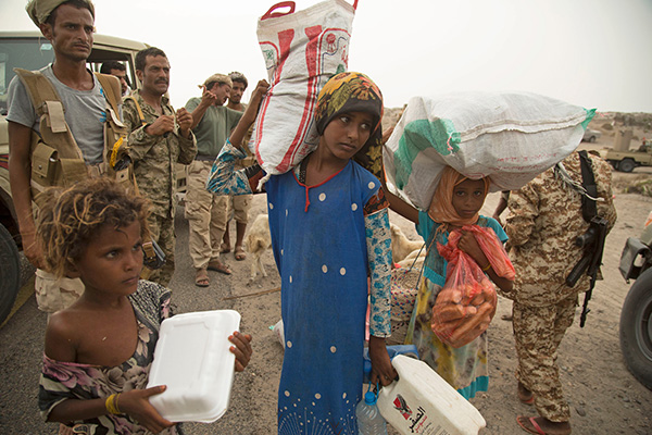Children carrying sacks and bags of food while soldiers stand in the background