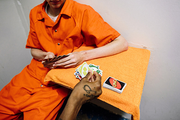 A teenager in an orange jumpsuit playing cards