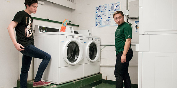 Two boys standing by washing machines