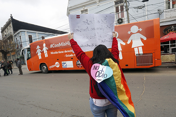 A woman wearing a rainbow flag and holding a sign